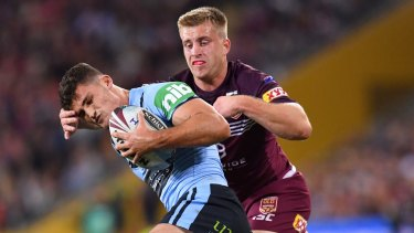 Under pressure: Nathan Cleary is tackled by Queensland playmaker Cameron Munster in Brisbane.