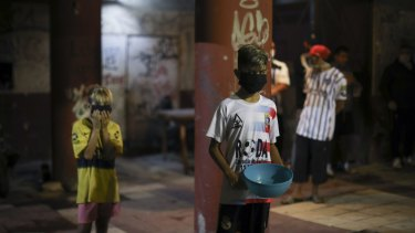 A child in a protective face mask and holding a container waits to be served at a soup kitchen on the outskirts of Buenos Aires.