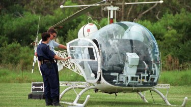 Police inspect the helicopter used to remove John Killick from Silverwater jail.