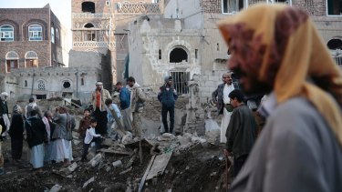People stand on the rubble of houses at the site of a Saudi-led airstrike near Yemen's Defence Ministry complex in Sanaa, Yemen, in November.