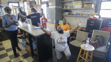 """Gail Russell, 68, falls to her knees and proclaims """"Thank you, Jesus"""" at Gloria's Corner Store in New Orleans, as she listens to the verdict on TV."""