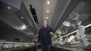 Brian Hassine, owner of Nuggets and Carats jewelry, stands near a hole in the ceiling where Chilean burglars broke in through the roof and stole more than $US1 million worth of jewelry and diamonds in Laguna Niguel, California.