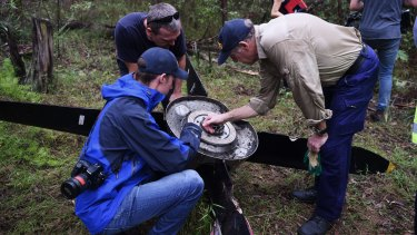 ATSB investigators and police examine the propeller that fell off an aircraft on approach to Sydney Airport.