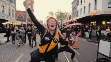 Richmond supporters on Swan Street celebrating their team's win over Adelaide during the 2017 grand final.