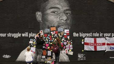 People place messages of support on a defaced mural of Marcus Rashford in his hometown.