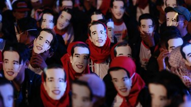 People wear masks depicting Indonesian President Joko Widodo during a rally.