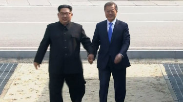 North Korean leader Kim Jong-un, left, crosses the border into South Korea, along with South Korean President Moon Jae-in for their historic face-to-face talks, in Panmunjom, in the DMZ.