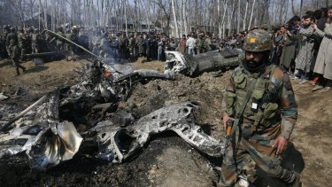 An Indian solider walks past the wreckage of an Indian aircraft after it crashed in the outskirts of Indian controlled Kashmir.