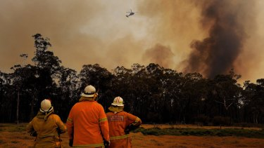 NSW RFS firefighters monitor a fire as a helicopter dumps water overhead at Tahmoor.
