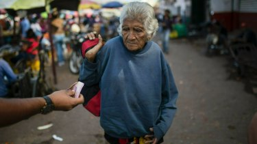 An elderly woman is offered cash as she begs at a wholesale food market in Caracas.