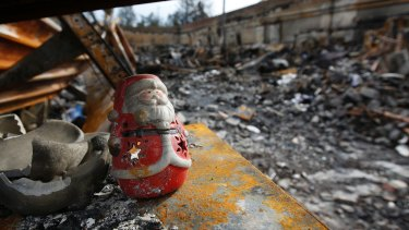 A Christmas decoration sits among the burned ruins of a California house after a 2018 wildfire.