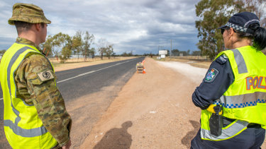 A soldier and police officer patrol Queensland's border with NSW near Hebel in central-southern Queensland before ADF personnel were withdrawn in September.