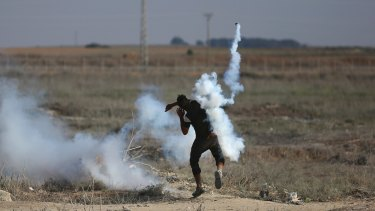 A Palestinian protester throws back a teargas canister fired by Israeli soldiers during clashes on the border with Gaza.