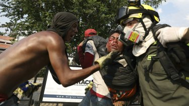 A Venezuelan youth, injured in clashes with Venezuelan National Guardsmen, is carried to a safe zone, at the Simon Bolivar International Bridge in La Parada, Colombia, on Monday.