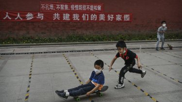 A young Chinese boy pushes a friend who wears a protective masks as he rides on his skateboard while they play at a small park in Beijing.