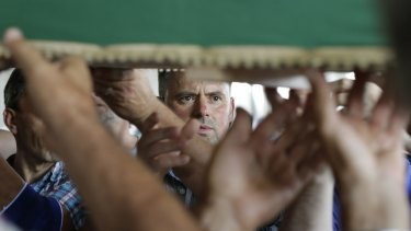 Bosnian Muslims carry one of 127 coffins with identified victims of the Srebrenica massacre in 2016.