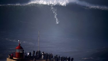 A surfer drops in on a large wave at Praia do Norte, in Nazare.