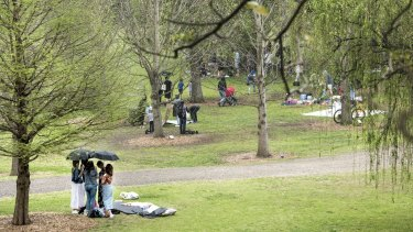 Picnics are packed up as the rain begins to fall at Centennial Park.