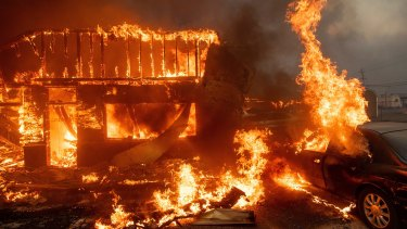 Flames consume a car and building in Paradise, California on November 8.
