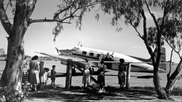 Flying Doctor being greeted by a group of waiting women and children