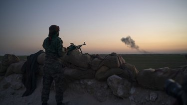 A US-backed fighter looks as smoke billows after an airstrike on territory still held by Islamic State militants outside Baghouz, Syria, in February. US President Donald Trump has said IS has now been defeated.