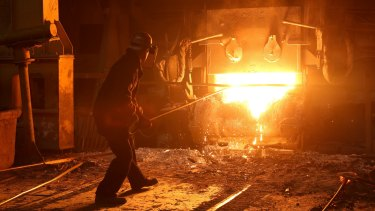 A worker cleans slag from an electric arc furnace in a steel plant in Russia.
