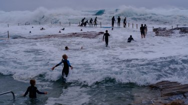 As large south swells lash the coast of NSW, kids swing from the chains of South Curl Curl rock pool.