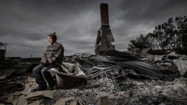 Angus McGillivery sits in the ruins of his Coyles road home near Terang after a bushfire ripped through the area.
