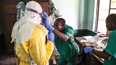 Health workers don protective clothing as they prepare to attend to patients in the isolation ward at Bikoro Hospital earlier this month.