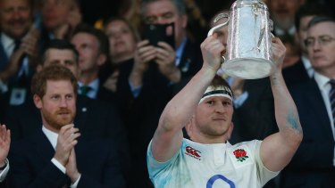 Prince Harry watches as England's Dylan Hartley holds up the Calcutta Cup in 2017.