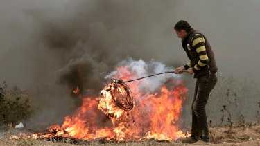A Palestinian protester burns tyres next to Gaza's border with Israel earlier this month.