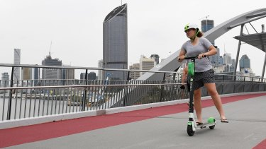 Lime users ride scooters through Goodwill Bridge in Brisbane, Tuesday.