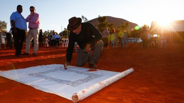 Indigenous leader Noel Pearson signs the canvas used for the Uluru Statement from the Heart's artwork in 2017.