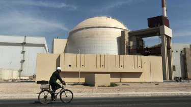 A worker rides a bicycle in front of the reactor building of the Bushehr nuclear power plant, in Iran, in 2010.
