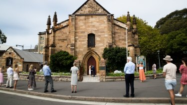Bystanders, who were not invited to the wedding, practice social distancing on the street while Brigette Leech and Matthew Selby are married by Minister Justin Moffatt, at the Garrison Church in Sydney.