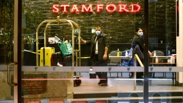 Masked workers inside the Stamford hotel during the quarantine program.