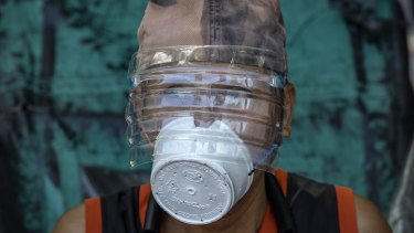 A man is seen wearing a makeshift mask made out of a styrofoam cup and a faceshield made out of a plastic bottle to protect against COVID-19 in Manila, Philippines.