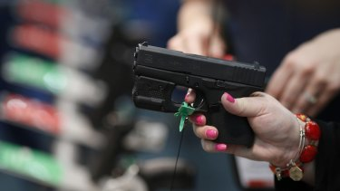 An attendee handles a firearm on the exhibit floor during the National Rifle Association (NRA) annual meeting in Louisville, Kentucky.