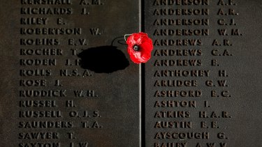 A poppy is placed on the Roll of Honour after the ANZAC Day dawn service at the Australian War Memorial.