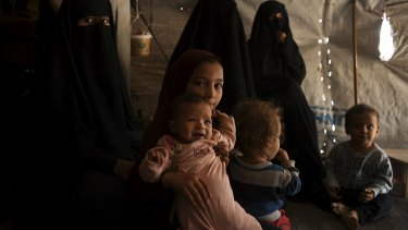 Nine-year-old Australian Maysa Assaad holds a baby in an al-Hawl camp tent.