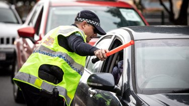 Police check cars for permits at a checkpoint in Coolangatta.
