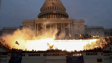 An explosion caused by a police munition is seen while supporters of US President Donald Trump gather in front of the US Capitol Building.