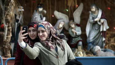 Muslim women take a selfie in front in Manger Square in front of the Church of the Nativity, revered as the site of Jesus Christ's birth, in the West Bank town of Bethlehem.