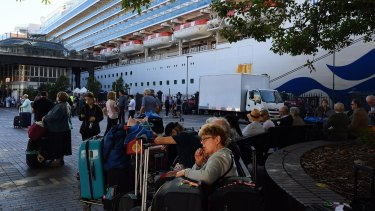 Passengers sit with their luggage after disembarking from the Ruby Princess cruise ship on March 19 at Circular Quay.
