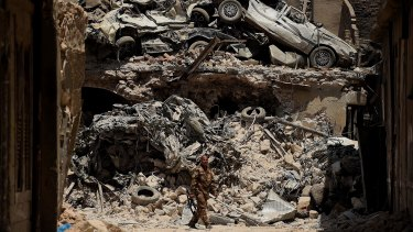 An Iraqi soldier walks past a wall of debris during the offensive to retake West Mosul in the northern summer of 2017.