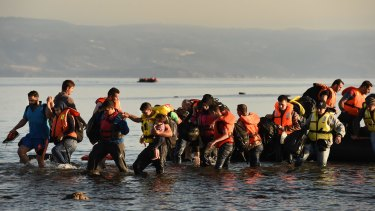 Refugees walk into the water as a boat with about 45 people from Syria, Iraq and Afghanistan aboard arrives at the Greek island of Lesbos after a three-hour journey from Turkey in 2015.
