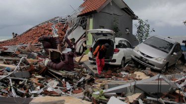 A man inspects the damage suffered by a building following a tsunami in Anyar, Indonesia.