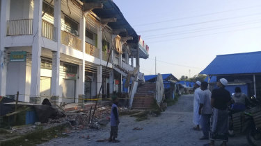 People survey a building partially damaged by earthquake in Poso, Central Sulawesi.