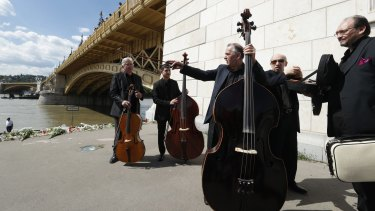 A musical group perform a lament in tribute to the victims on the banks of the Danube River on Saturday.