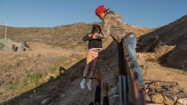 A migrant from Honduras pass a child to her father after he jumped the border fence to get into the US side to San Diego, California this month.